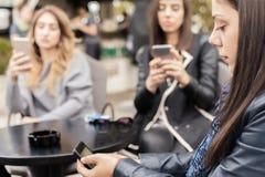 Kvinna tre i kafé genom att använda app-smartphonen som spelar det sociala nätverket Fotografering för Bildbyråer