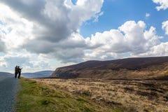 Kvinna två i förgrunden som ser berg och himmel i de Wicklow bergen royaltyfria bilder
