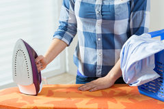 Kvinna under att stryka för kläder Fotografering för Bildbyråer