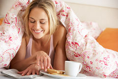 Kvinna under duveten som äter frukosten Royaltyfri Fotografi