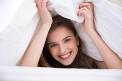 Kvinna under filten i sängen Arkivfoton
