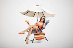 Kvinna under strandparaplyet Arkivbild