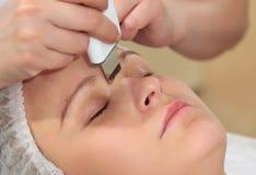 Kvinna under tillvägagångssätt av den ultraljuds- ansiktsbehandlingen Royaltyfri Fotografi