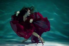 Kvinna under vattnet i en röd klänning fotografering för bildbyråer