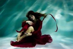 Kvinna under vattnet i en röd klänning arkivbild