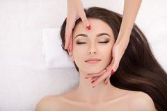 Kvinna under yrkesmässig ansikts- massage i skönhetbrunnsort royaltyfri bild