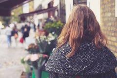 Kvinna utanför en blomsterhandlare Royaltyfri Fotografi