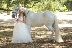Kvinna utomhus med en vit häst Arkivfoto