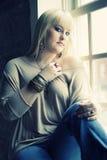 Kvinna vid fönstret Fotografering för Bildbyråer
