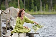 Kvinna vid vattnet med en krans i hennes h?nder arkivfoto
