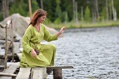 Kvinna vid vattnet med en krans i hennes h?nder fotografering för bildbyråer