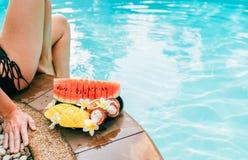 Kvinna weared baddräkt som sitter på simbassängsida med plattan av tropiska frukter royaltyfria foton