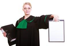 Kvinnaadvokatadvokaten i klassikerpolermedelkappa rymmer det tomma tecknet för skrivplattan royaltyfria bilder