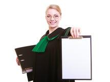 Kvinnaadvokatadvokaten i klassikerpolermedelkappa rymmer det tomma tecknet för skrivplattan royaltyfri bild