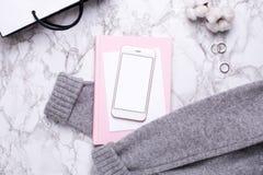 Kvinnaaffärsdagen med mobiltelefonen och den rosa anteckningsboken marmorerar på tabellen royaltyfri bild