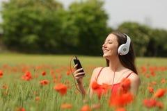 Kvinnaandning och lyssnande musik i ett fält Arkivbild