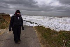 Kvinnaanseende av kust- erosion som äger rum under en vinterstorm Många hem för en tid sedan har förlorats i denna gemenskap tack royaltyfria foton