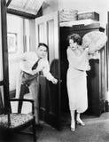 Kvinnaanseende bak en dörr som försöker att slå en man med en kudde (alla visade personer inte är längre uppehälle, och inget god Arkivbilder