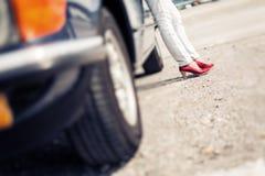 Kvinnaanseende bredvid den konvertibla klassiska bilen Arkivfoton