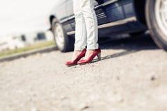 Kvinnaanseende bredvid den konvertibla klassiska bilen Royaltyfri Foto