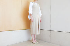Kvinnaanseende i beige klänning för hörn med minsta moderiktig stil för mitt- hälsko royaltyfri foto