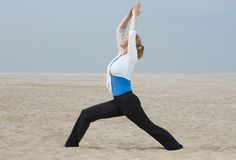 Kvinnaanseende i yogaposition på stranden Arkivfoto