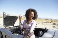 Kvinnaanseende med hennes bil Arkivfoto