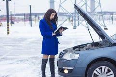 Kvinnaanseende nära huven av bilen och försiktigt att studera den manuella bilen Royaltyfria Bilder