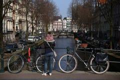 Kvinnaanseende på en bro över den Amsterdam kanalen bredvid bicy två royaltyfri fotografi