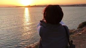 Kvinnaanseende på klippan som tar en bild av solnedgången över havet arkivfilmer