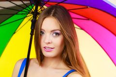 Kvinnaanseende under det färgrika regnbågeparaplyet royaltyfria foton