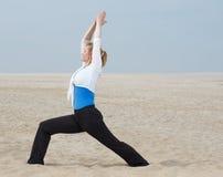 Kvinnaanseendet i yoga poserar på stranden Arkivbild