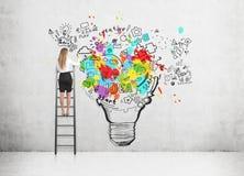 Kvinnaanseendet på en stege och teckningen en stor och färgrik ljus kula skissar på en betongvägg arkivbilder