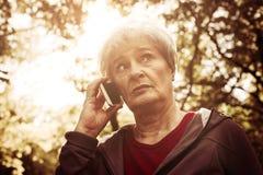 Kvinnaanseendet parkerar in och ha konversation på mobil royaltyfria bilder