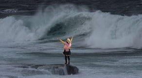 Kvinnaanseendet vaggar på framme av vågor arkivfoto