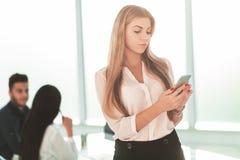 Kvinnaanst?lld av f?retagssitayaen SMS p? hennes smartphone royaltyfri foto