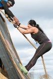 Kvinnaansträngningar som klättrar väggen i extremt lopp för hinderkurs Royaltyfri Fotografi