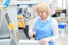Kvinnaarbetare i borttagningen för tvätteriprocessfläck royaltyfria foton