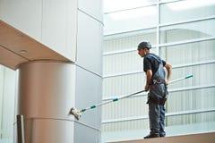 Kvinnaarbetare som gör ren det inomhus fönstret fotografering för bildbyråer