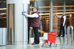 Kvinnaarbetare som gör ren den inomhus inre Royaltyfri Foto