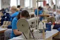 Kvinnaarbete i en filt startar fabriken Royaltyfri Bild