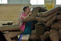 Kvinnaarbete i en filt startar fabriken Royaltyfria Bilder