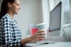 Kvinnaarbete på datoren som dricker från den återvinningsbara Takeaway koppen arkivfoto