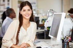 Kvinnaarbete på skrivbordet i upptaget idérikt kontor Arkivbild