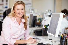 Kvinnaarbete på skrivbordet i upptaget idérikt kontor