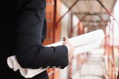 Kvinnaarbete som teknikern Holding Building Plans arkivbild