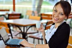 Kvinnaarbeten som har en kopp av kaffe Arkivbild