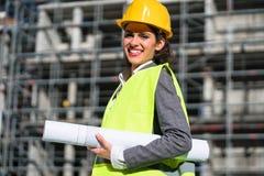Kvinnaarkitekt med konstruktionsplan på byggnadsplatsen Fotografering för Bildbyråer