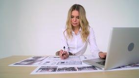 Kvinnaarkitekt på arbete i hennes kontor som arbetar på nytt projekt; handteckningar, datorteckningar stock video