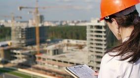 Kvinnaarkitekten kontrollerar konstruktionsplatsen lager videofilmer